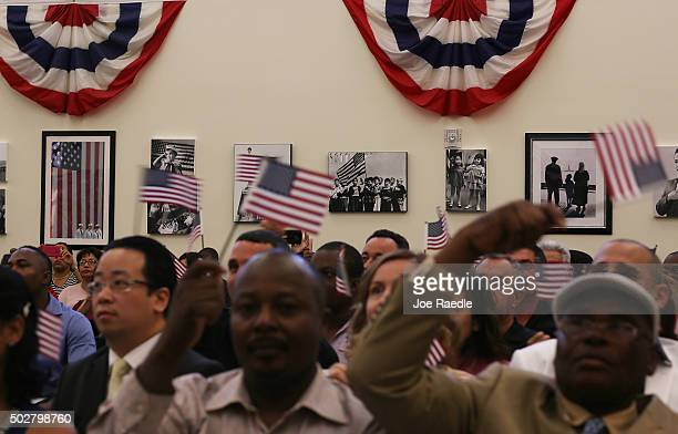 Pictures of past citizenship services are seen on the wall as people wave American flags after being sworn in during a citizenship ceremony at the US...