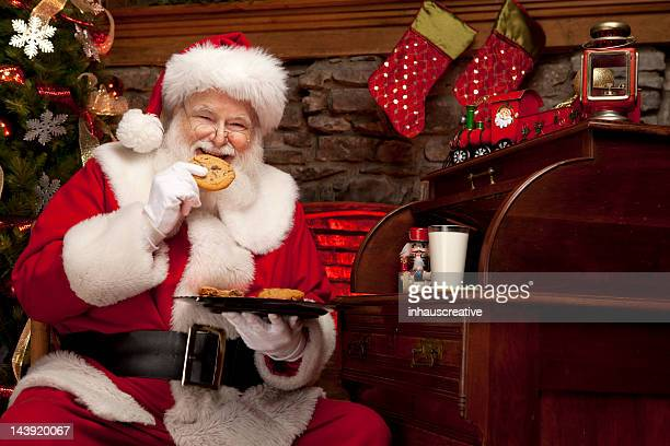 pictures of real santa claus enjoying milk and cookies - santa claus stock pictures, royalty-free photos & images