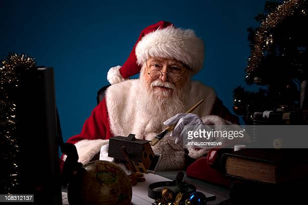 pictures of real santa claus working late at night - santas workshop stock photos and pictures