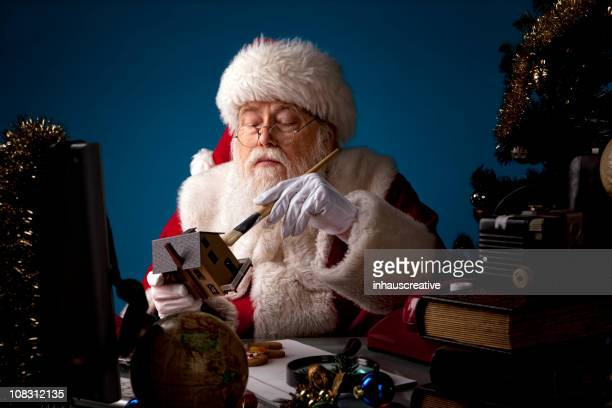 pictures of real santa claus working late - santas workshop stock photos and pictures