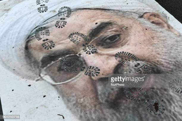 Pictures of Ruhollah Khomeini and Hassan Rohani are stomped by the protesters in front of the ambassy of Iran against the arrestations and the...