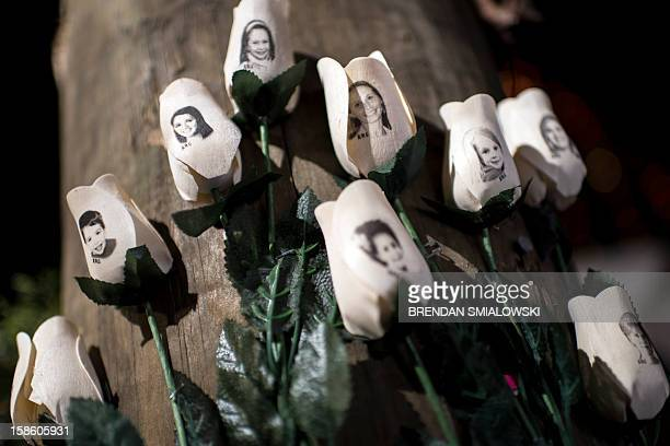 Pictures of victims of the Sandy Hook Elementary School shooting are seen on artificial roses at a roadside memorial December 20 2012 in Newtown...