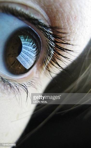 A pictures shows binary code reflected from a computer screen in a woman's eye on October 22 2012 AFP PHOTO / LEON NEAL