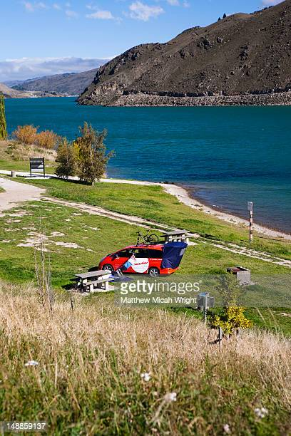 A picturesque photo stop alongside Lake Wakatipu at a spot called Champagne. A Spaceship camper van sets up a campsite alongside the lake