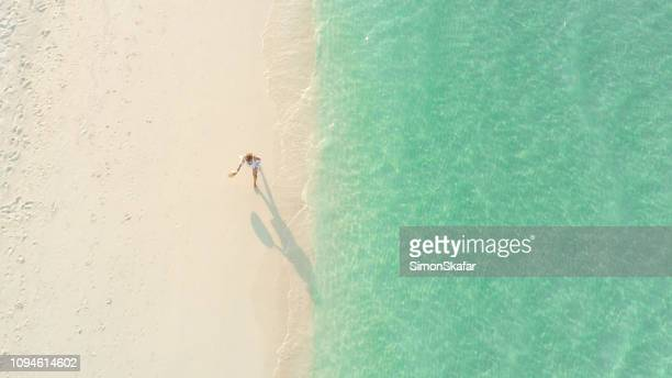 picturesque seascape with walking woman,maldives - praia imagens e fotografias de stock