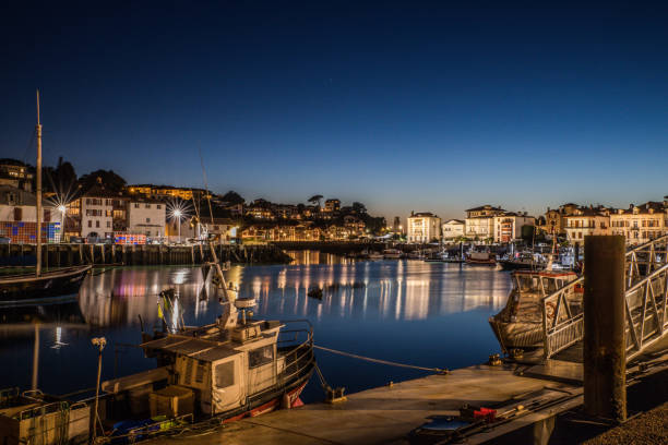 Picturesque view of city harbor with moored boats and illuminated buildings reflected in calm water under blue night sky in french Pais Vasco