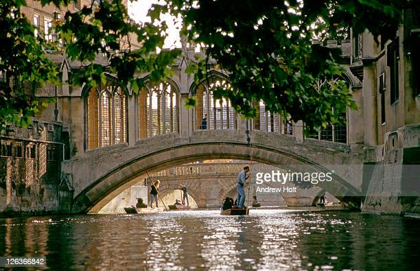 A picturesque view of the Bridge of Sighs in Cambridge, with people punting under the bridge and along the river Cam. The Bridge of Sighs in Cambridge is a bridge belonging to St. John's College of Cambridge University. It was built in 1831 and crosses the