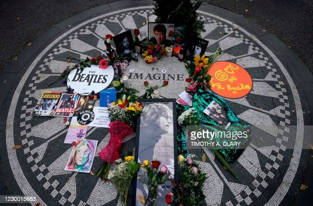 Picturs are seen on a monument as mourners gather on the 40th anniversary of John Lennon's death, at Strawberry Fields, in Central Park to honor the...