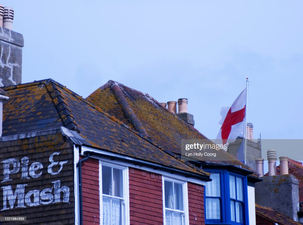 Pie and Mash sign on a wall of traditional British building with English flag. : Stock Photo