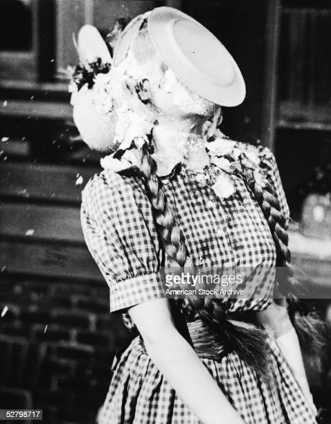 A pie on a plate strikes an unidentified actress with pigtails in the face and knocks her bonnet off in a film still from an unknown movie 1930s
