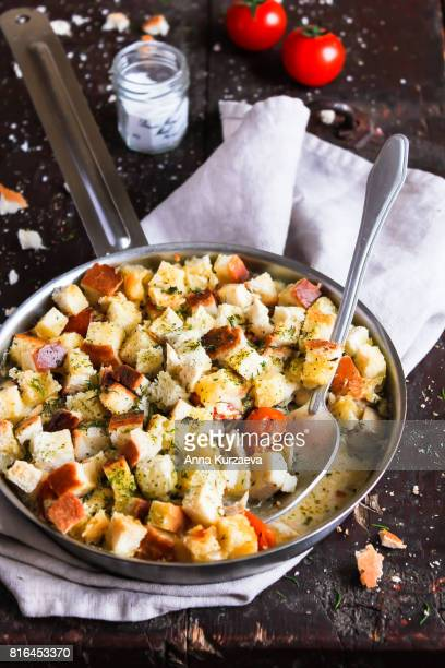 Pie with white fish, cherry tomatoes, cream sauce and bread in a pan on a wooden table, selective focus