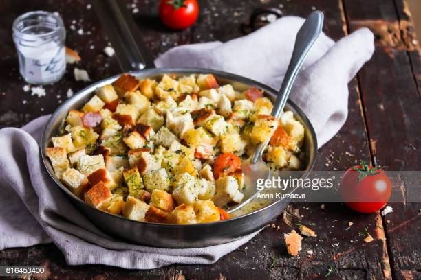 pie with white fish, cherry tomatoes, cream sauce and bread in a pan on a wooden table, selective focus - crouton stock photos and pictures