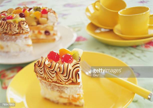 A piece cut of fruitcake and dishes on table