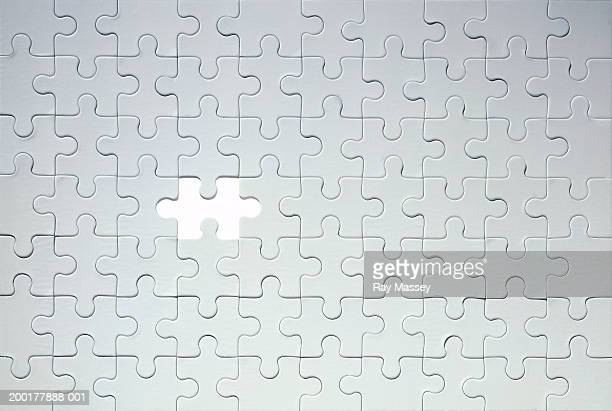 piece missing from grey jigsaw puzzle - raadsel stockfoto's en -beelden