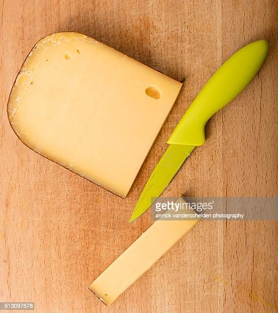 piece of aged cheese and a knife on wooden chopping board. - 西フランダース ストックフォトと画像