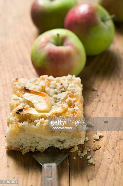Piece of apple crumble cake, fresh apples in background