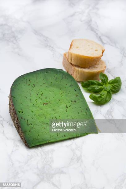 Piece of basil cheese, kitchen knife, bread and basil leaves on marble