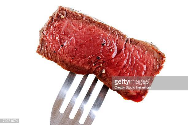 Piece of beef filet on fork, close-up