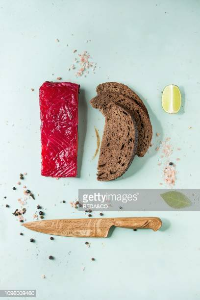 Piece of beetroot marinated salted salmon with sliced rye bread pink salt pepper lime and wooden knife over light green pinup style background Top...