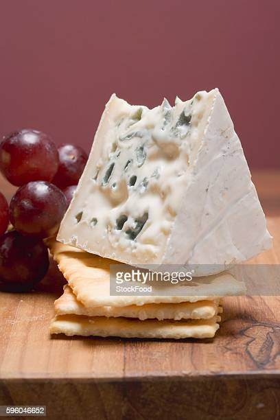 Piece of blue cheese with crackers and red grapes