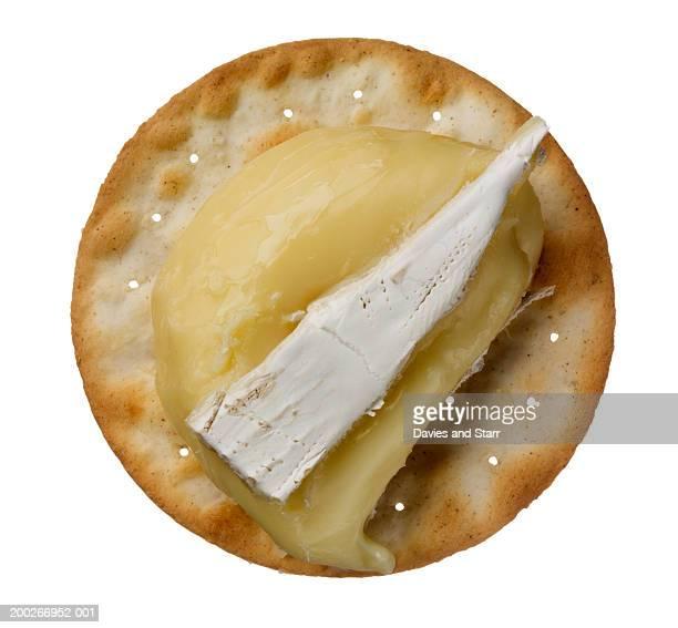 piece of brie on cracker, overhead view - brie stockfoto's en -beelden