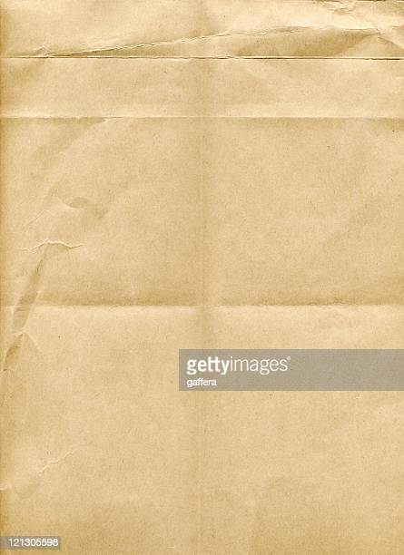 A piece of brown paper with fold marks and creases