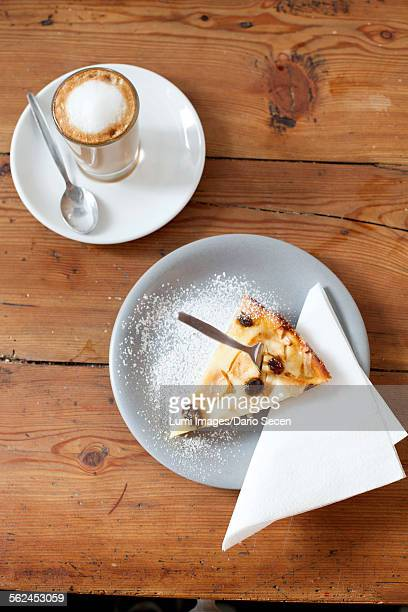 Piece of cake and latte on table