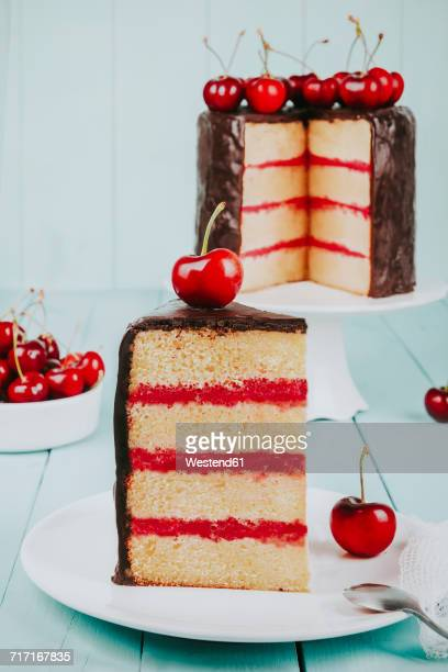 Piece of cake with chocolate icing and cherries on plate
