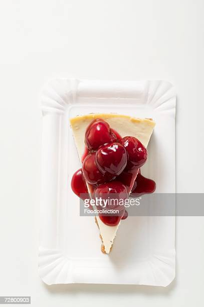a piece of cheesecake with cherry sauce - paper plate stock photos and pictures