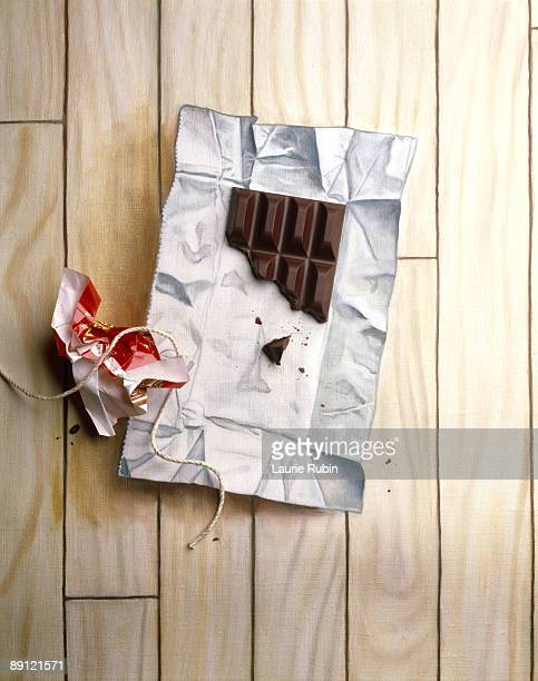 piece of chocolate bar on painted wrapper - candy wrapper stock photos and pictures