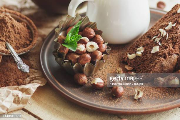 piece of chocolate cake, mint leaves, hazelnuts and jar with milk - theobroma imagens e fotografias de stock