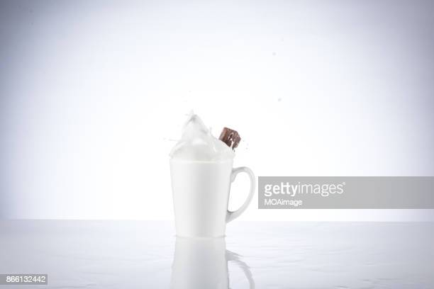 A piece of chocolate splashing in the cup of milk