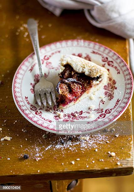 Piece of fruit pie or galette with figs and raspberry on a dessert plate