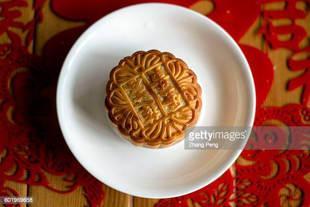 A piece of Mooncake is put on red papercut window decoration On September 15 Chinese people will celebrate 2016 MidAutumn festival by getting...