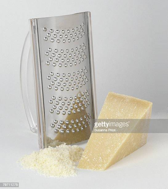 Piece of parmesan cheese, fine-toothed grated, and a small pile of grated parmesan.