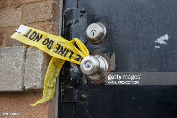 Piece of police caution tape is seen on the front door of the building where a shooting took place in Chicago, Illinois, on March 14, 2021. - At...