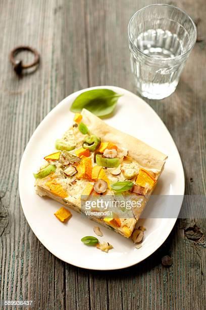 Piece of pumpkin leek quiche with hazelnuts and basil