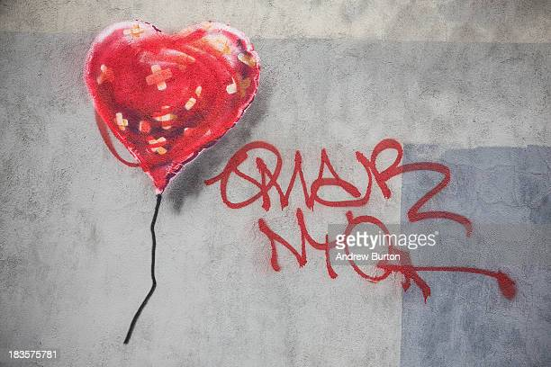 A piece of street art depicting a heartshaped balloon covered in bandages allegedly done by the street artist Banksy is seen on October 7 2013 in the...