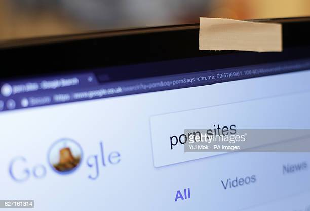 A piece of tape covering a laptop's webcam with a porn search typed into the Google Chrome internet browser in London
