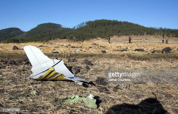 A piece of the fuselage of ET Flight 302 can be seen in the foreground as local residents collect debris at the scene where Ethiopian Airlines Flight...
