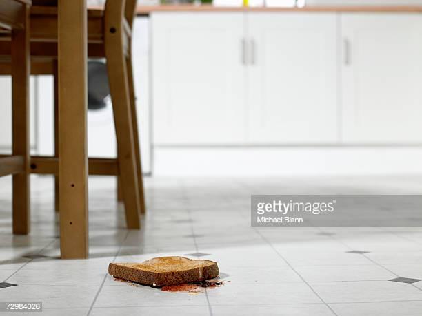 Piece of toast lying jam side down on kitchen floor