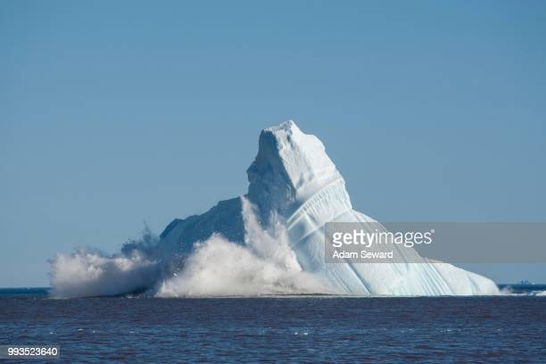 Pieces breaking off an enormous iceberg causing it to unbalance and collapse, Qeqertarsuaq, Disko Bay, Greenland