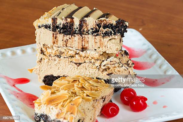Pieces of butterscotchchocolate cake with dry fruit chips and cherries placed on a white serving plate
