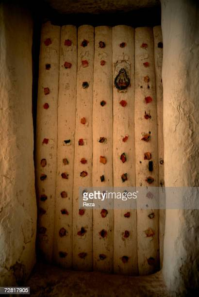 Pieces of coloured cloth hang on a palm tree wooden door which is the sign of a journey to Mecca or a wedding taking place in the home April 2000 in...