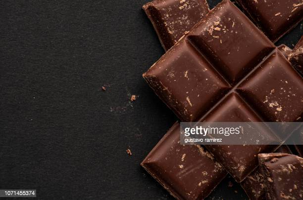 pieces of dark chocolate on black background - chocolate stock pictures, royalty-free photos & images