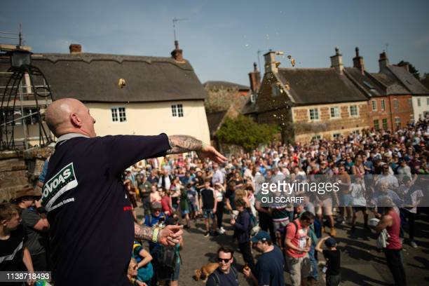 Pieces of hare pie are thrown into the crowd for the 'scramble' during the Easter Monday Hallaton Hare Pie Scrambling and Bottle Kicking traditional...