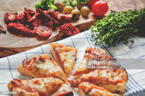 Pieces of Margarita pizza on a napkin with sun-dried tomatoes and olives with a large bundle of...