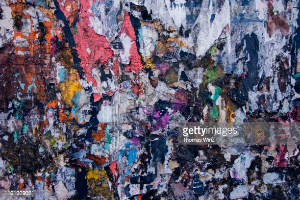 pieces of old paper posters on a wall - placard stock pictures, royalty-free photos & images