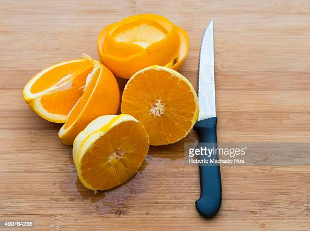 Pieces of orange fruit and its peel on a wooden chopping board with a knife The oranges are peeled and cut into half while the peel is cut to form a...
