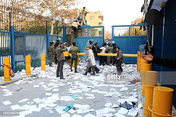 Pieces of paper are strewn across the floor as police clear protesters back through a security gate following a break in at the British Embassy...